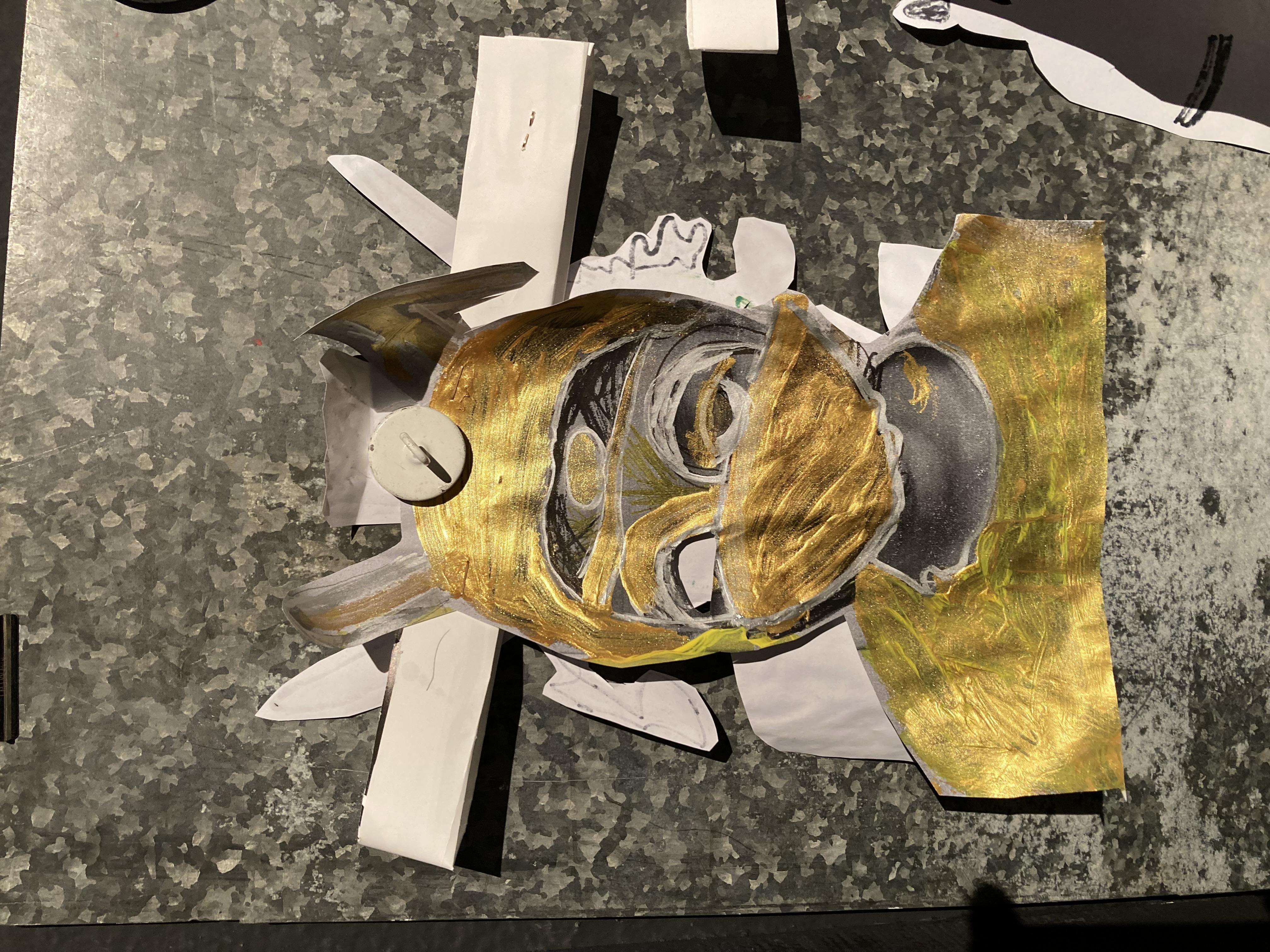 ein schwarz weißes A4-großes Foto eines Schülers wurde mit goldener und weißer Farbe so übermalt, das es wie eine goldene Maske erschein, die nur noch wenig vom ursprünglichen Gesicht erkennen lässt.