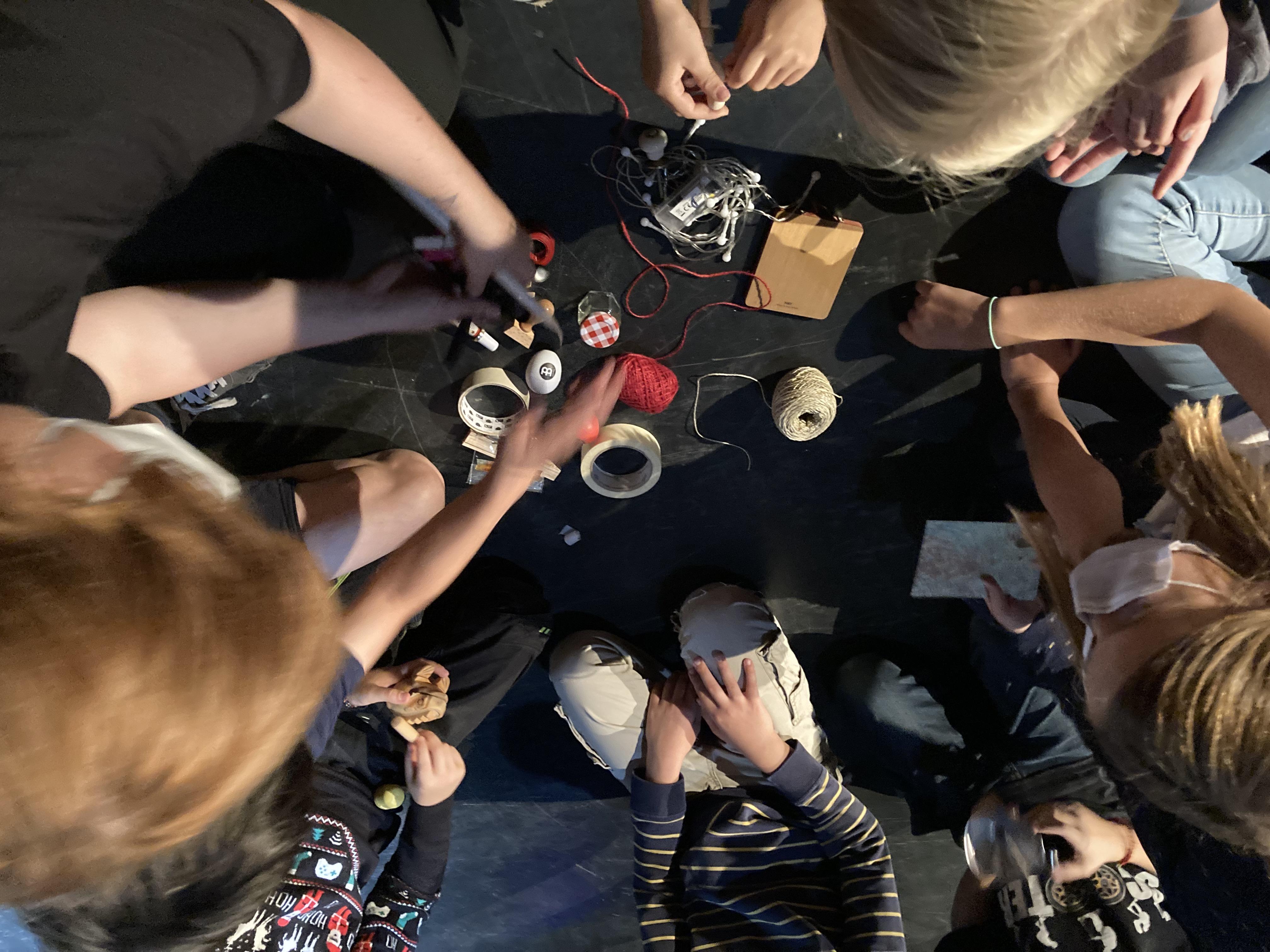 mehrere Kinder sitzen um einen Kreis von kleinen Lieblingsdingen, wie bspw. einer Schachtel, einer Rolle roten Fadens, kleinen Steinen, einem Stift. Sie bringen die Dinge ob ihres Aussehens oder ihrer Funktion in eine Reihenfolge als kreisförmige Schnecke
