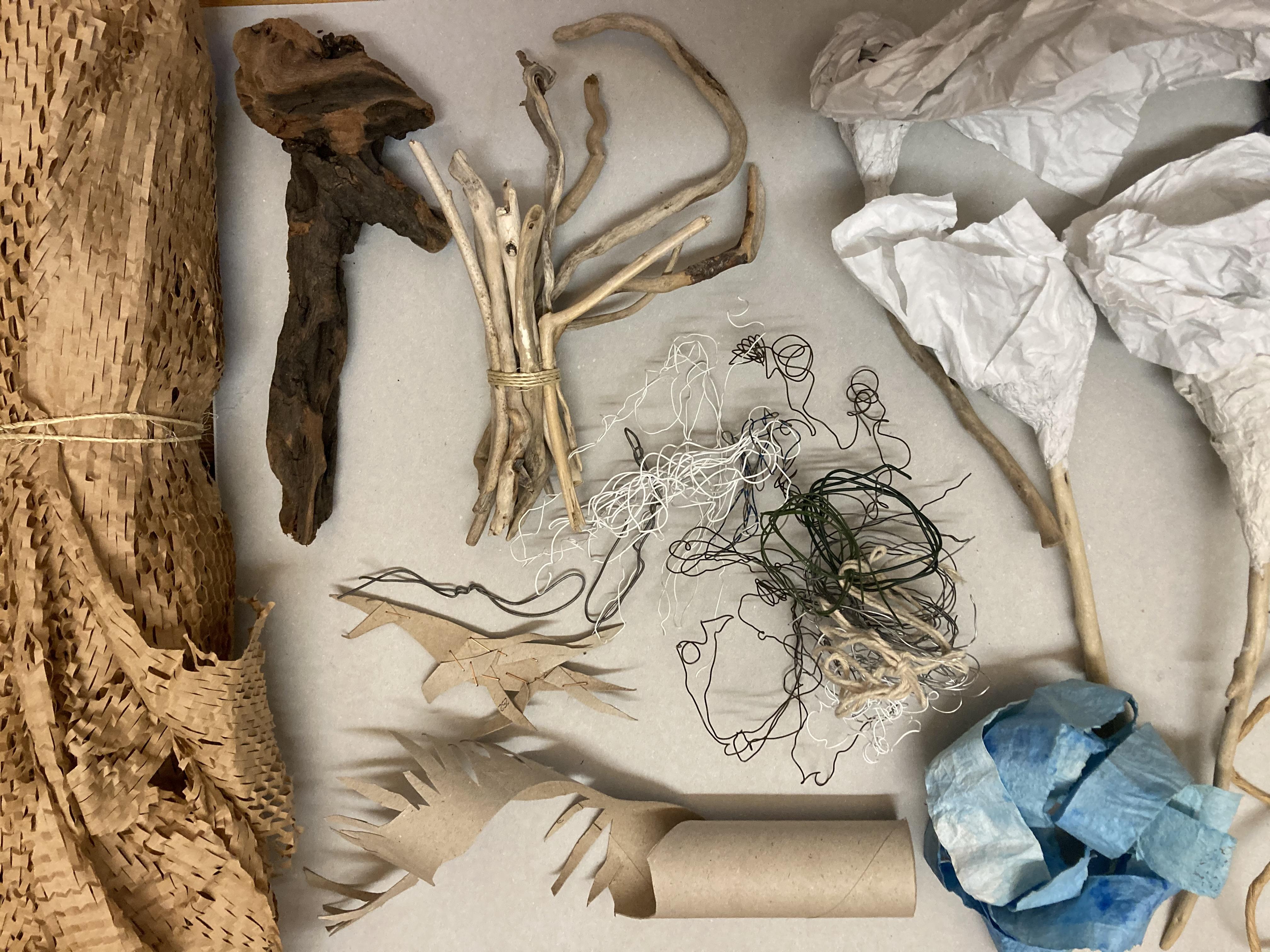 Verschiedene, nebeneinander angeordnete Materialien: eine zusammengerollte Stroh- oder Bastmatte, Stöckchen, Schnüre, eine Papprolle, geknülltes Papier, Stoff.