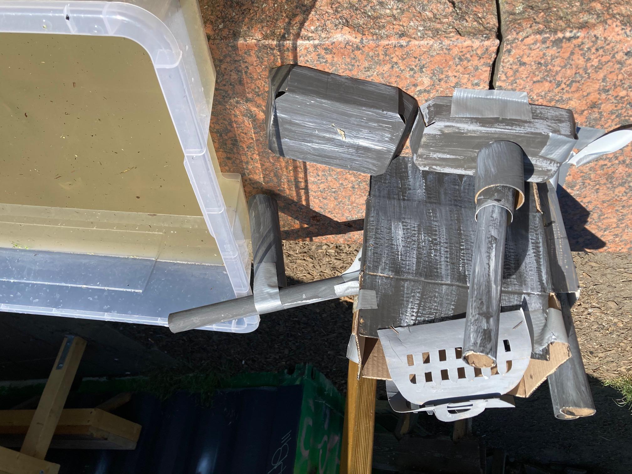 Eine kleine graue Fabrik aus Kartons mit langen Röhren steht neben einem Wasserbecken mit verschmutztem schlammigen Wasser auf einer Steinmauer