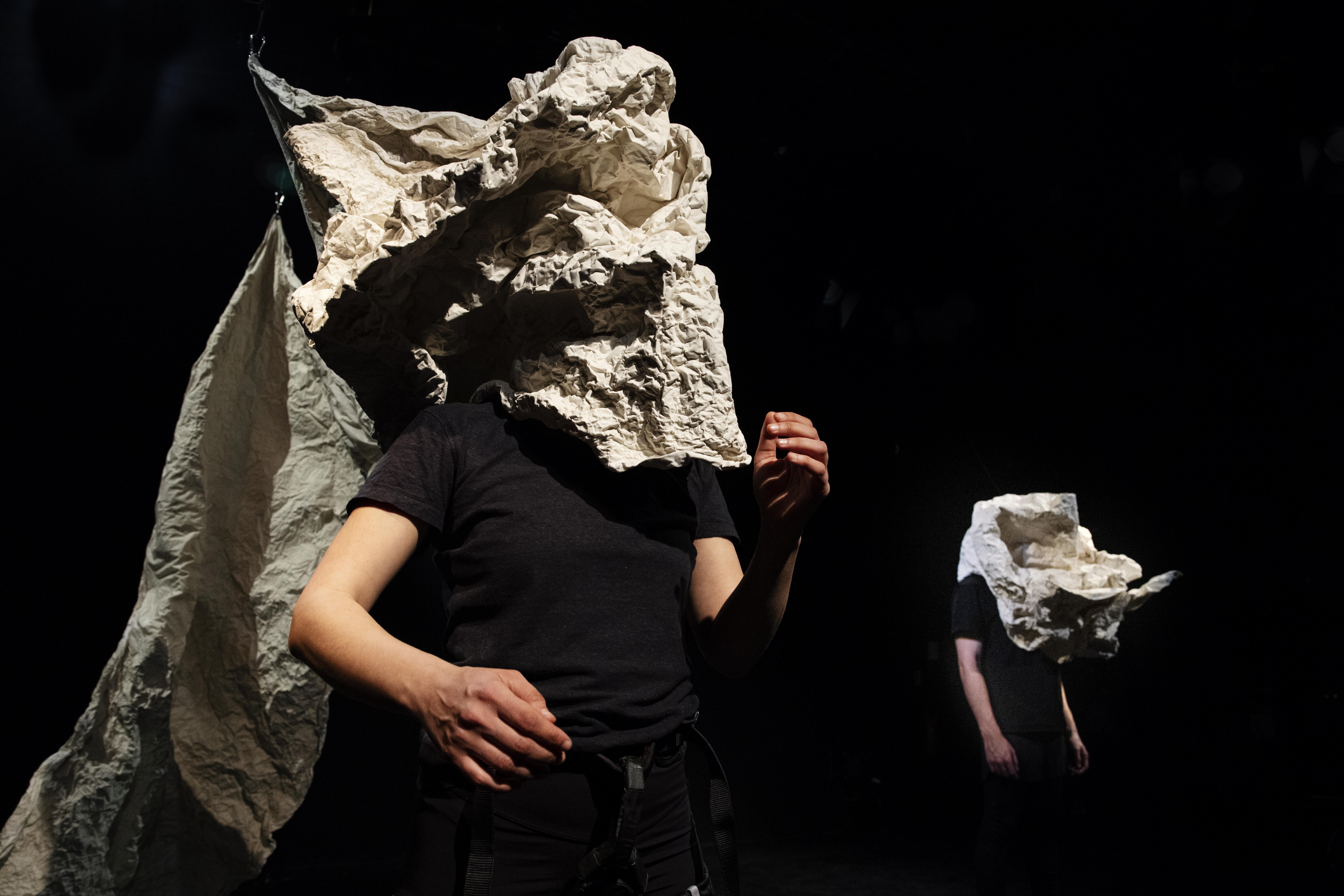 auf der Bühne stehen zwei Spieler*innen mit großen geformten Masken aus weißer formbarer Folie
