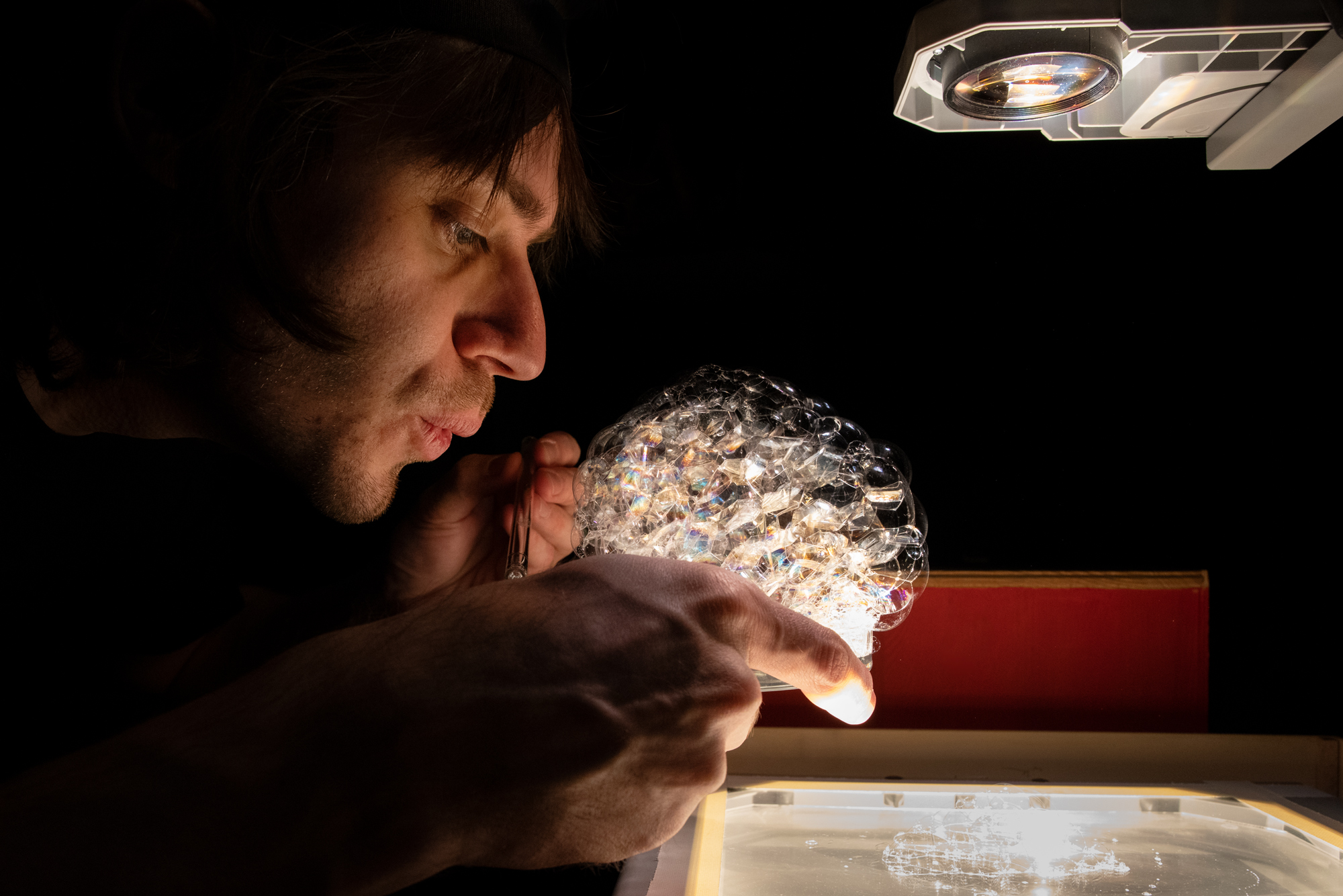 ein Spieler macht mit einem Trinkhalm Seifenblasen vor einer beleuchteten Fläche