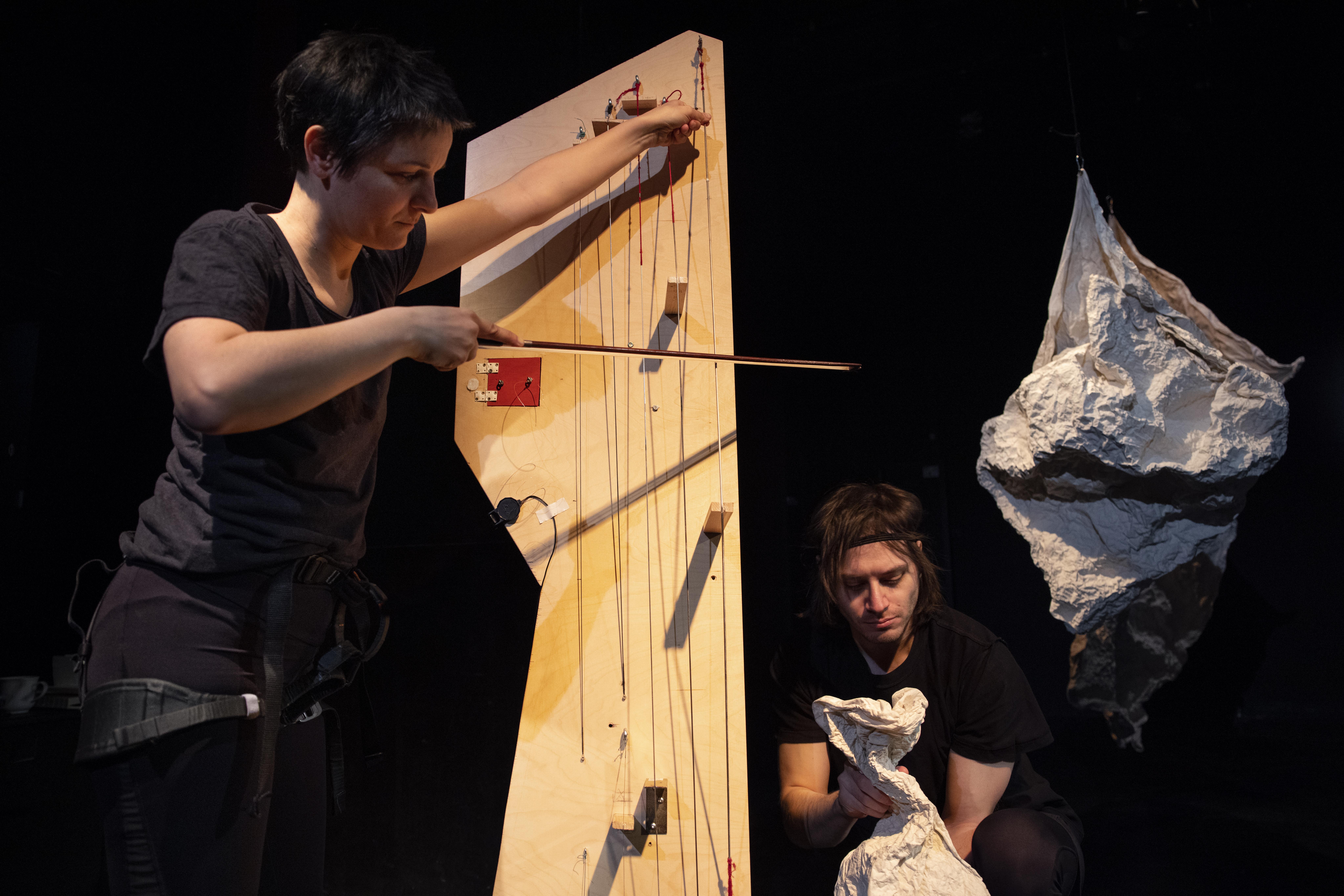 die Spielerin streicht mit einem Bogen über ein Brett mit Saiten, daneben hockt ein zweiter Spieler mit einer formbaren Folie, im Hintergrund hängt eine weiße geformte Skulptur