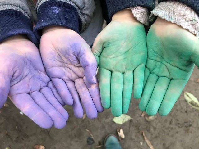 gefärbe Hände in grün und voilett nach einer Klopfaktion