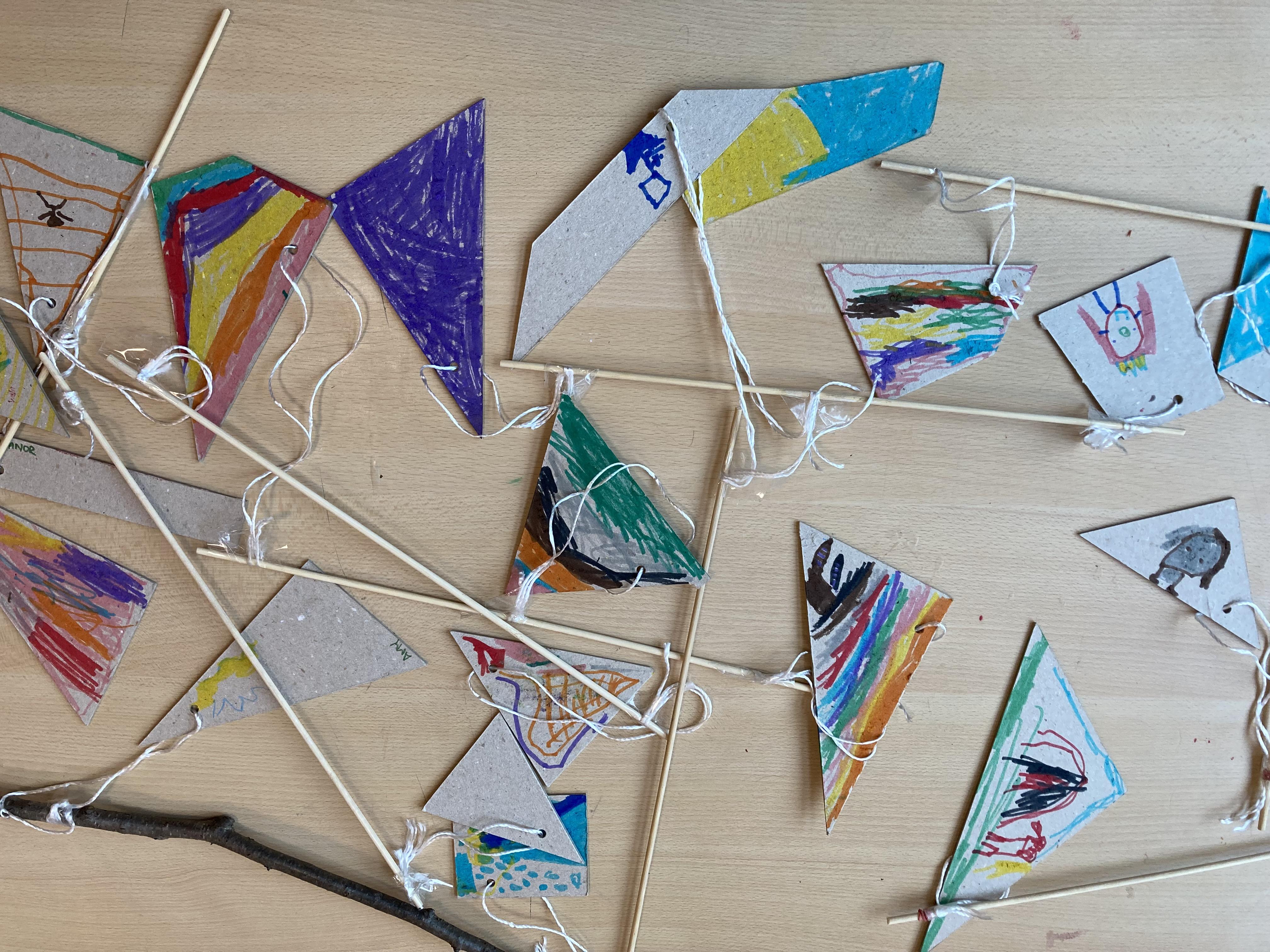 auf einem Tisch liegen verstreut Stäbe, an denen jeweils 2 Ecken aus Pappe angebracht sind. Auf den pappen sind gezeichnete Motive der Kinder in bunten Farben