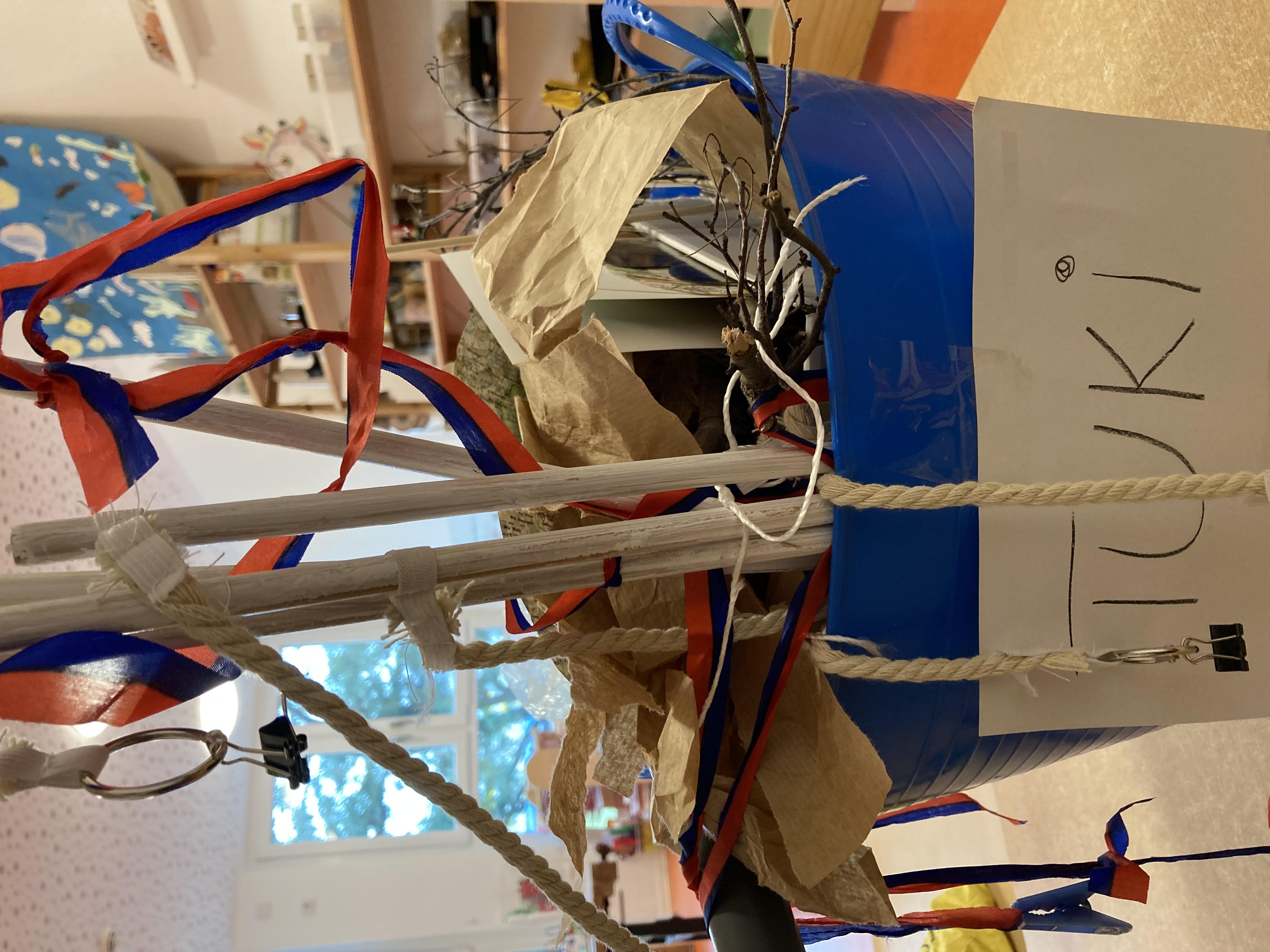 eine blaue Wanne mit vielen Materialien wie Papiere, Zweige, Bänder, Draht steht auf einem Tisch. Vorn auf der Wanne steht TUKI