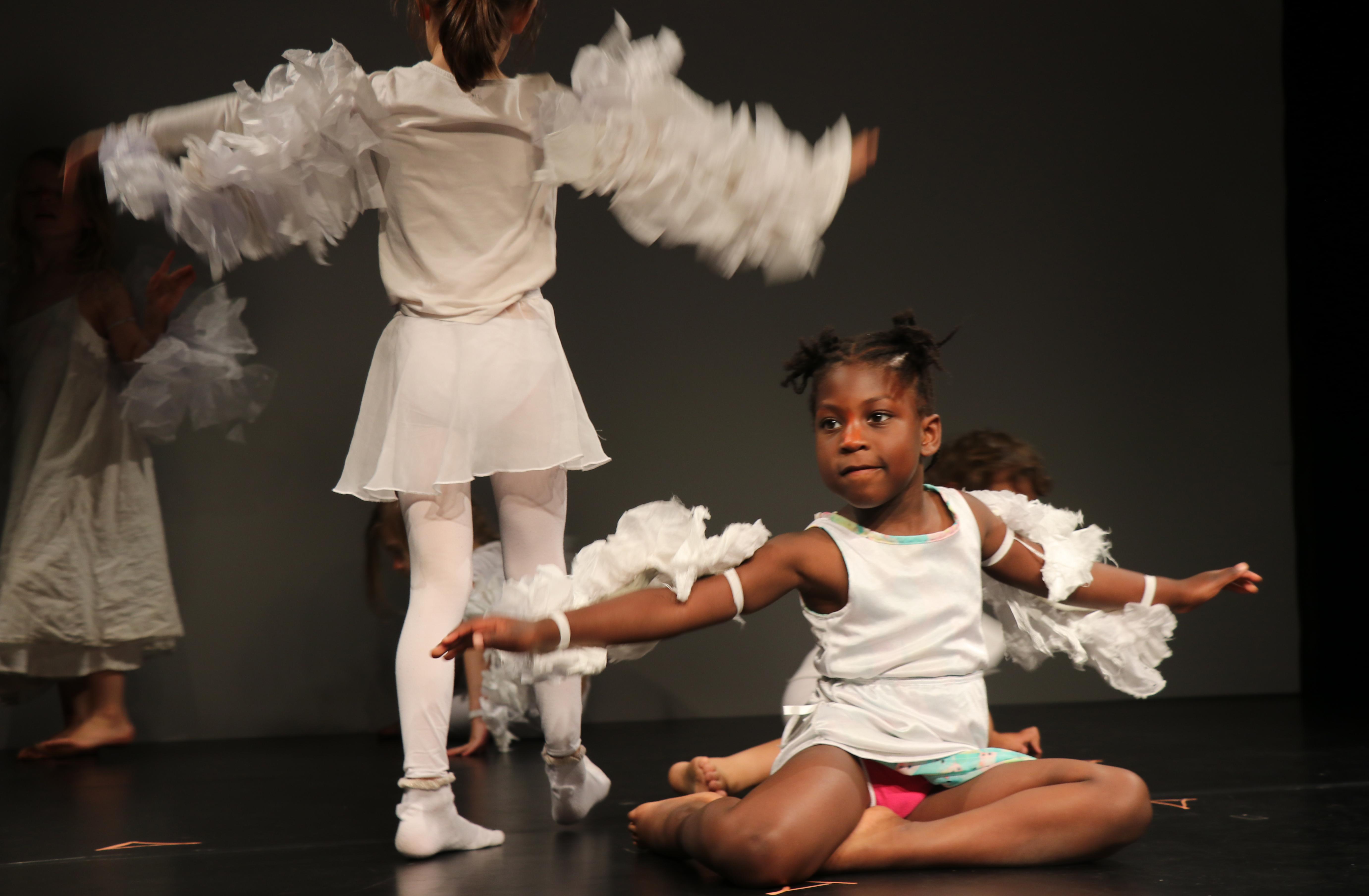 Ein Mädchen sitzt mit seitlich untergeschlagenen Beinen auf der Bühne. Sie breitet die Arme aus, an denen mit Riemchen weiße Flügel aus einem watteähnlichen Material angebracht sind und hat ein weißes Kleid ohne Ärmel an. Links neben ihr steht ein weiteres Mädchen mit weißem Kleid und weißer Strumhose, die ebenfalls die befkügelte Arme ausbreitet. Im Hintergrund ist noch ein Kind mit Flügeln abgebildet, das halb verdeckt ist.
