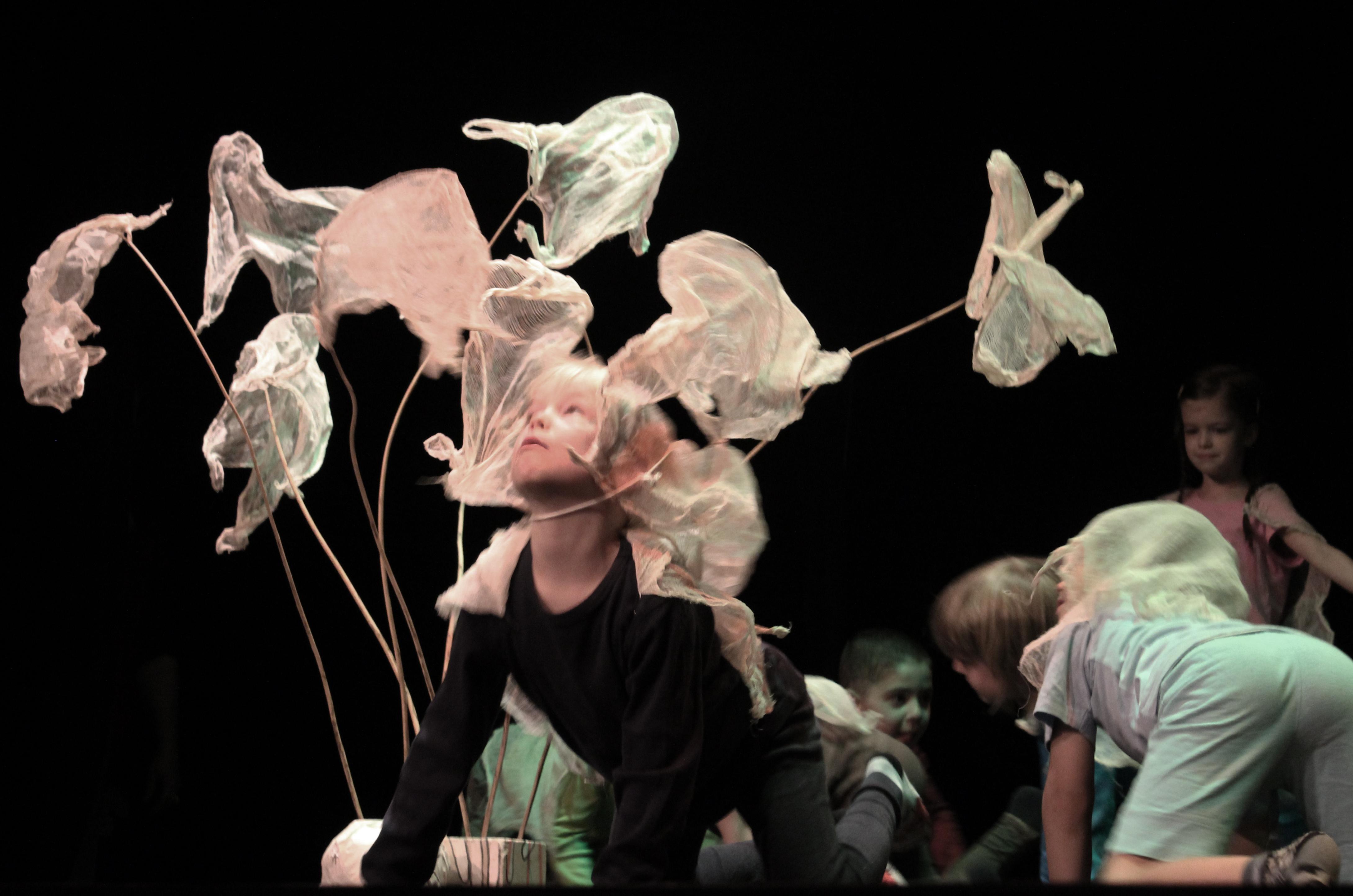 Ein etwa siebenjähriger Junge mit schwarzer Kleidung kniet im Vierfüßlerstand auf der Bühne und schaut nach oben. Um sie herum sind etwa zehn gebogene Stäbe abgebildet, an denen in verschiedenen Formen flatternde Plastiktüten bzw. Teile davon angebracht sind. Im Hintergrund des dunklen Raumes sind weitere knieende Kinder zu sehen.