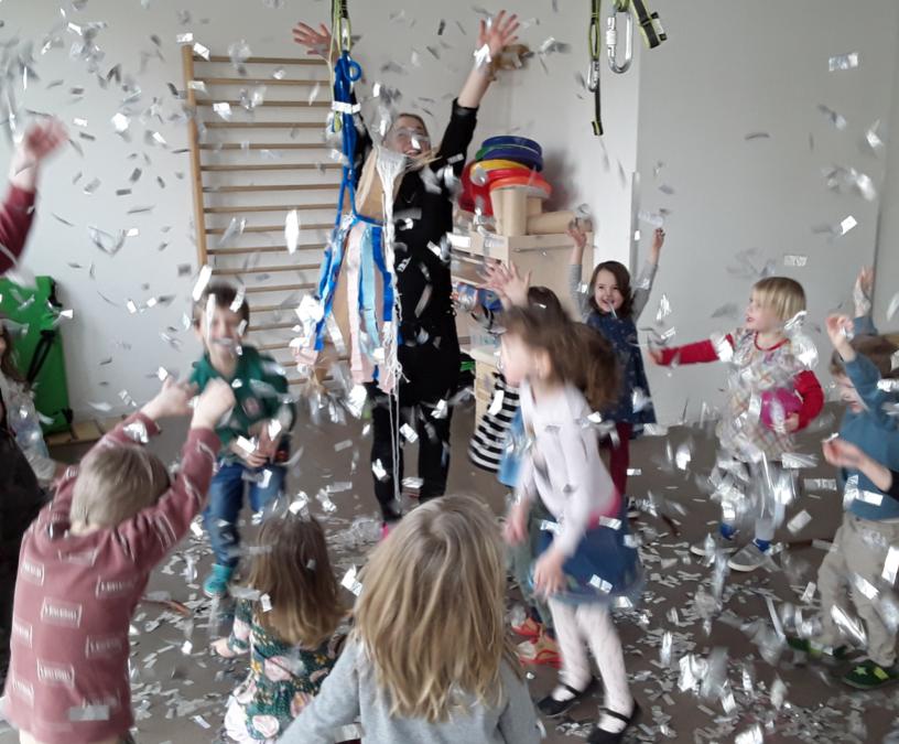 Zu sehen sind etwa zehn Kinder und ein Erwachsener, die kleine Schnipsel Papier oder Folie in die Luft wirbeln, Im HIntergrund ist eine Sprossenwand zu sehen.