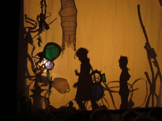 Schattenprojektion aus Silhouetten und Material auf gelb angeleuchtetem Hintergrund. Die seitlichen Schatten von zwei Kindern sind zu sehen sowie filigrane Formen, die an Türme erinnern. Oben zeichnet sich der Schatten einer Fischreuse ab.