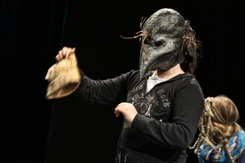 Mädchen mit einer schwarzen, geschnäbelten Maske, die einen Gegenstand aus Stoff hochhält. Rechts daneben ist noch ein weiteres Mädchen von hinten zu sehen. Der Hintergrund ist schwarz.