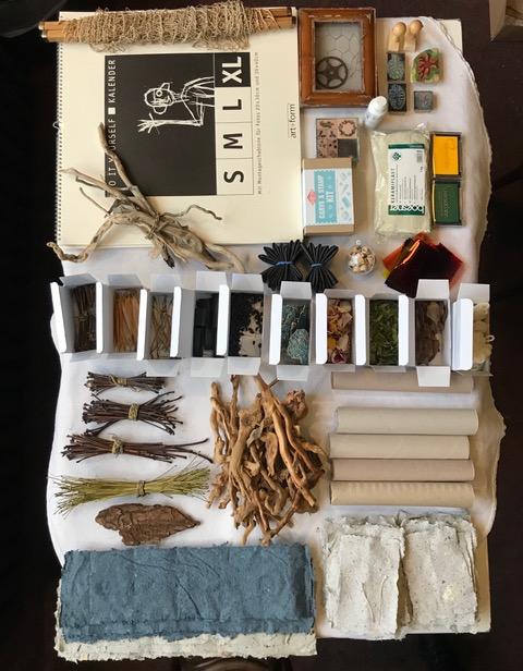 Ansammlung von fein säuberlich sortierten Materialien: Stöckchen, Papier, Papprollen, Gräser und anderes.