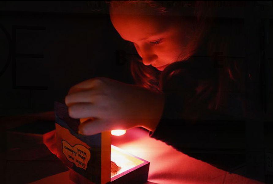 Kind schaut in eine beleuchtete Kiste