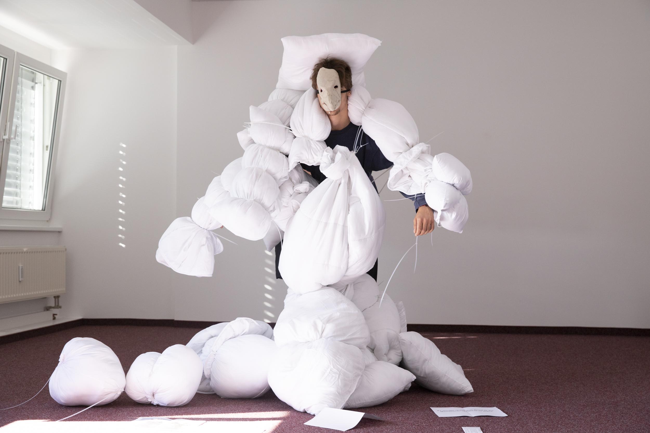 ein Spieler steht mit mehreren weißen Stoffbündeln am Körper und ausgebreiteten Armen verschnürt und einer weißen Maske im Gesicht im Raum