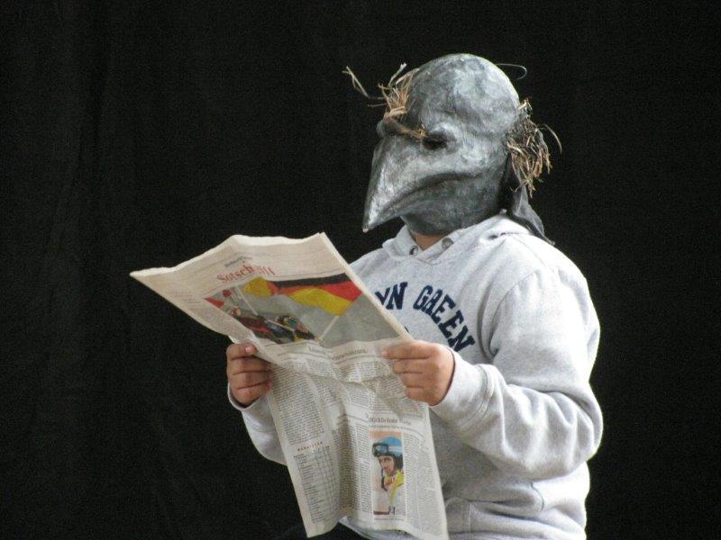 Ein Spieler steht mit einer grauen Vogelmaske mit spitzem Schnabel zeitungslesend im Bild