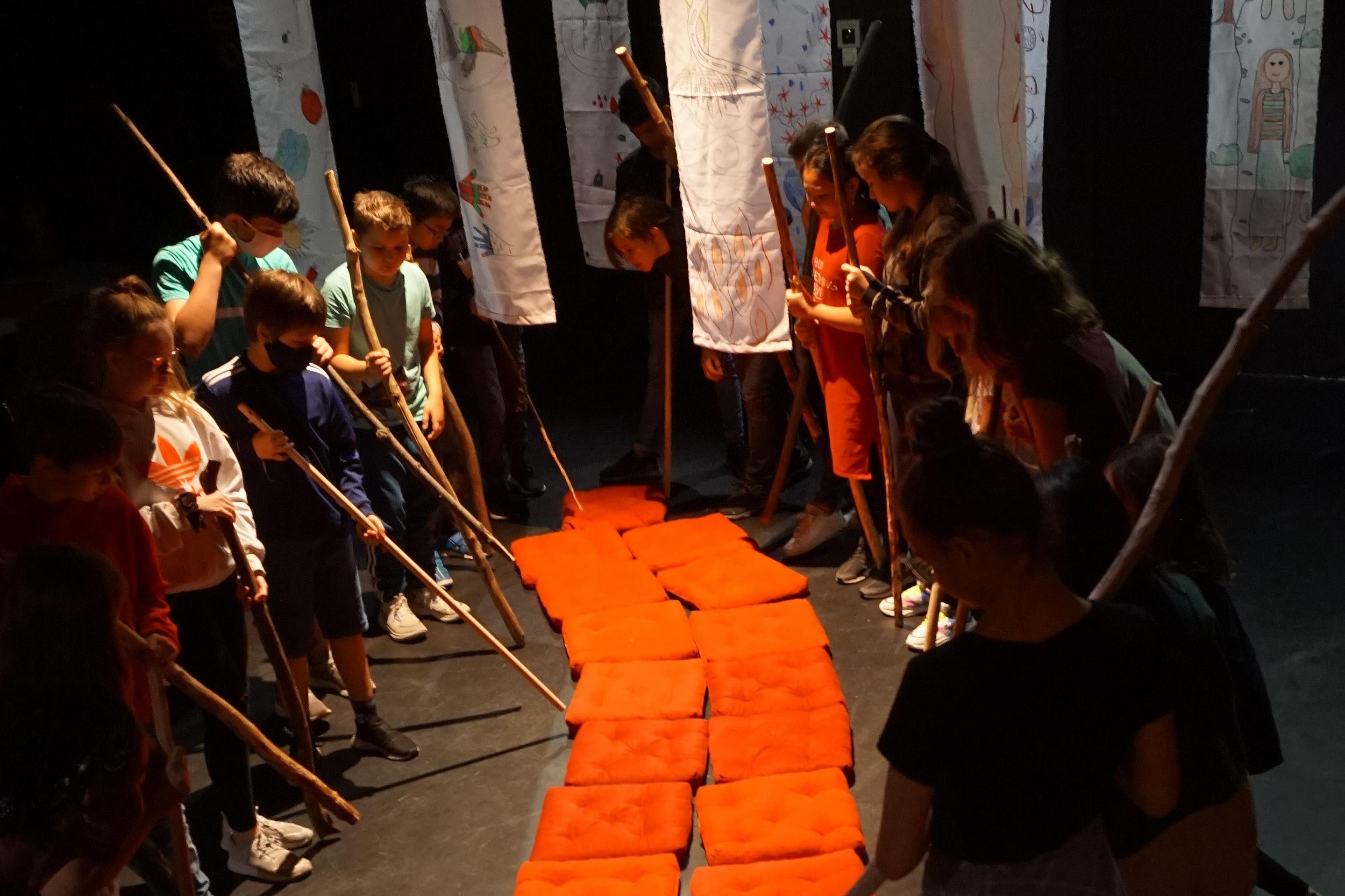 Etwa fünf Kinder stehen sich auf der Bühne gegenüber. Sie richten lange Stöcke auf aneinandergereihte rote Sitzkissen, die wie ein Fluss zwischen ihnen wirken. Im Hintergrund hängen mit Kinderzeichnungen bemalte Stoffbahnen von der Decke herab.