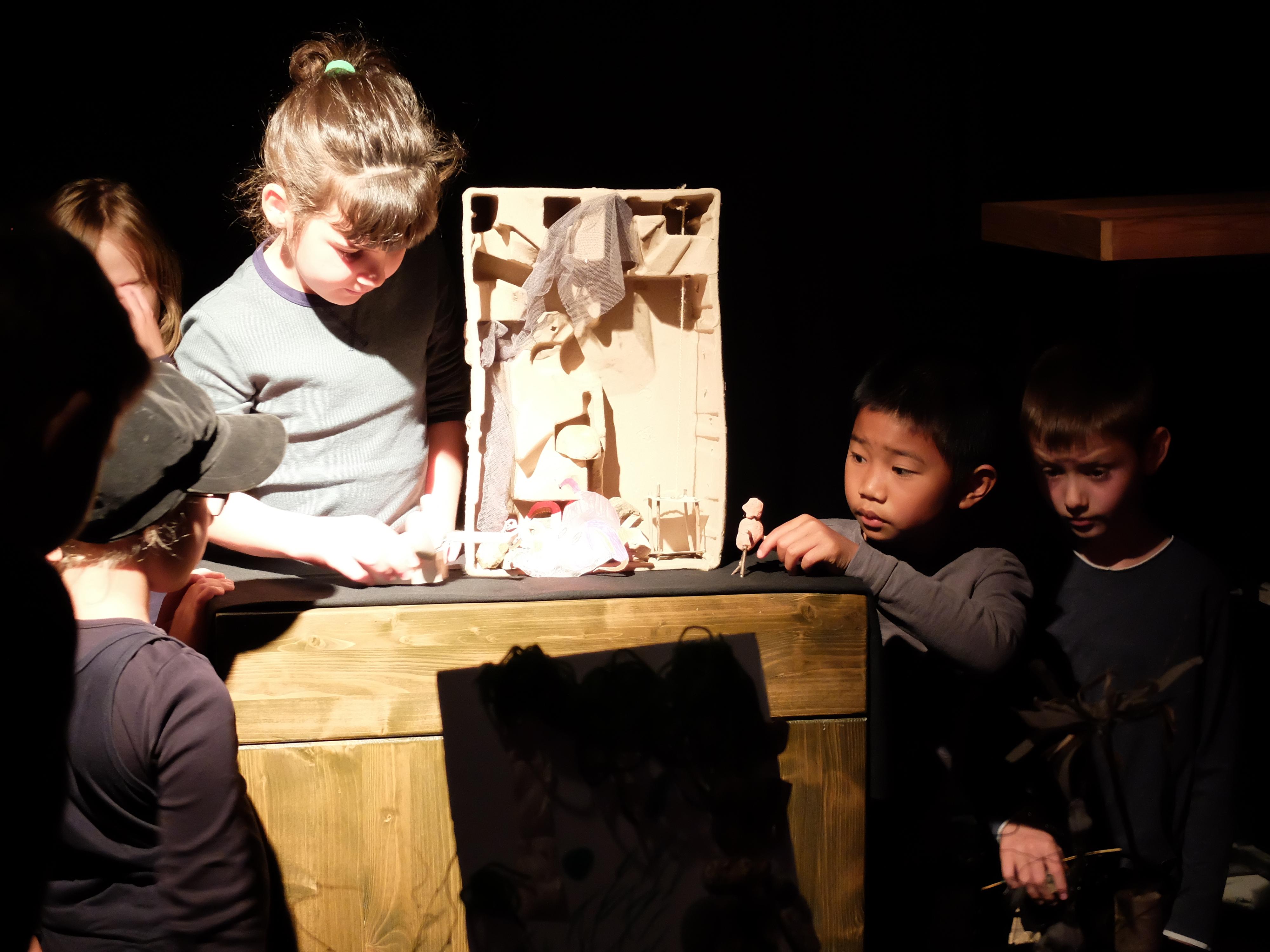 Ein hell angeleuchtes Mädchen mit Zopf steht hinter einem Holzschränkchen auf der Bühne. Darauf befindet sich hochkant eine rechteckige Pappkiste, in der Dinge aus Stoff und Pappe wie in einem Mini-Bühnenbild angeordnet sind. Neben ihr stehen im Halbdunkel je zwei andere Kinder. Eines davon hält eine kleine Figur aus Knete in der Hand.