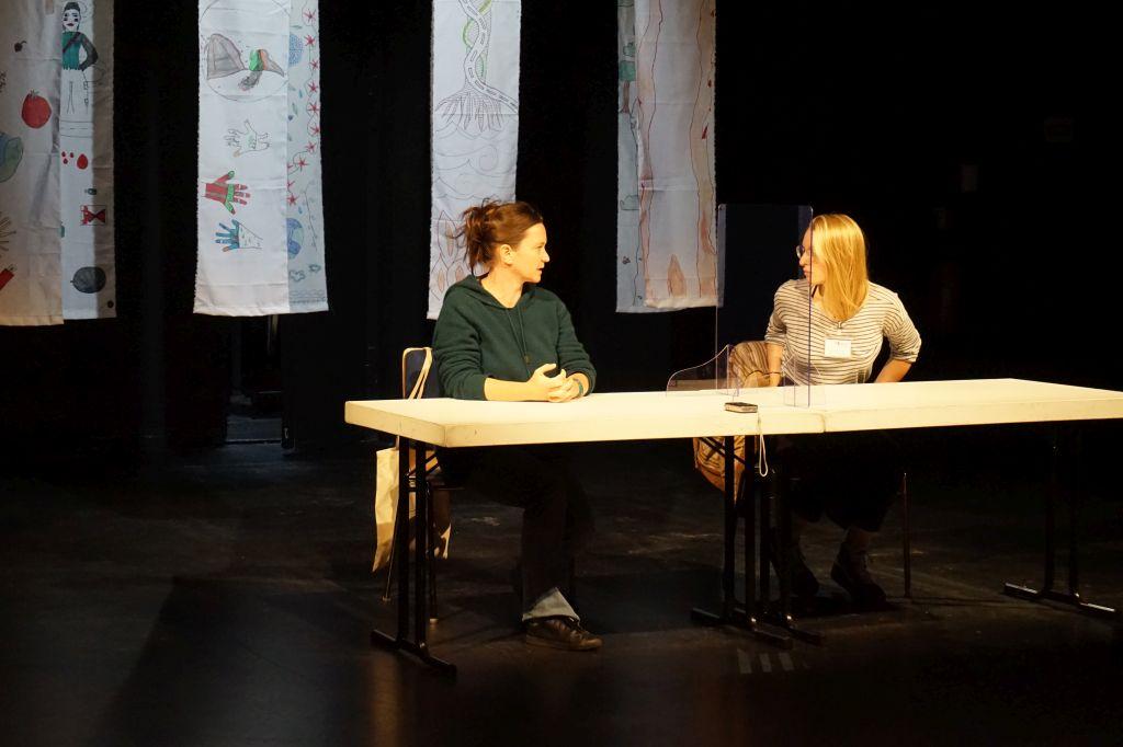 Autorin und Übersetzerin sitzen an einem hell erleuchteten Tisch vor dem Bühnenbild aus herabhängenden, bemalten Stoffbahnen. Sie sind einander im Gespräch zugewandt.