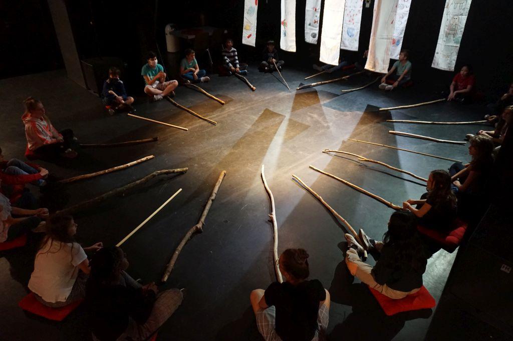 Etwa zwanzig Kinder sitzen im Halbdunkel der Bühne in einem Kreis. Vor ihnen liegen je zur erleuchteten Kreismitte hin ausgerichtet lange Stöcke. Weiter hinten im Bild hängen acht bemalte Stoffbahnen von der Decke herab.