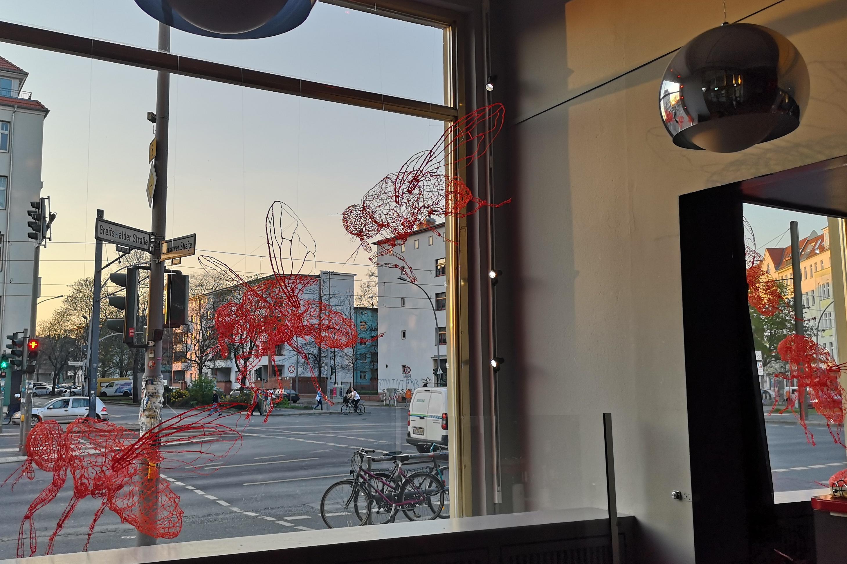 Aus filigranem rotem Plastik bestehende großformatige Fliegen in den Fenstern der Schaubude, Sicht aus dem Foyer