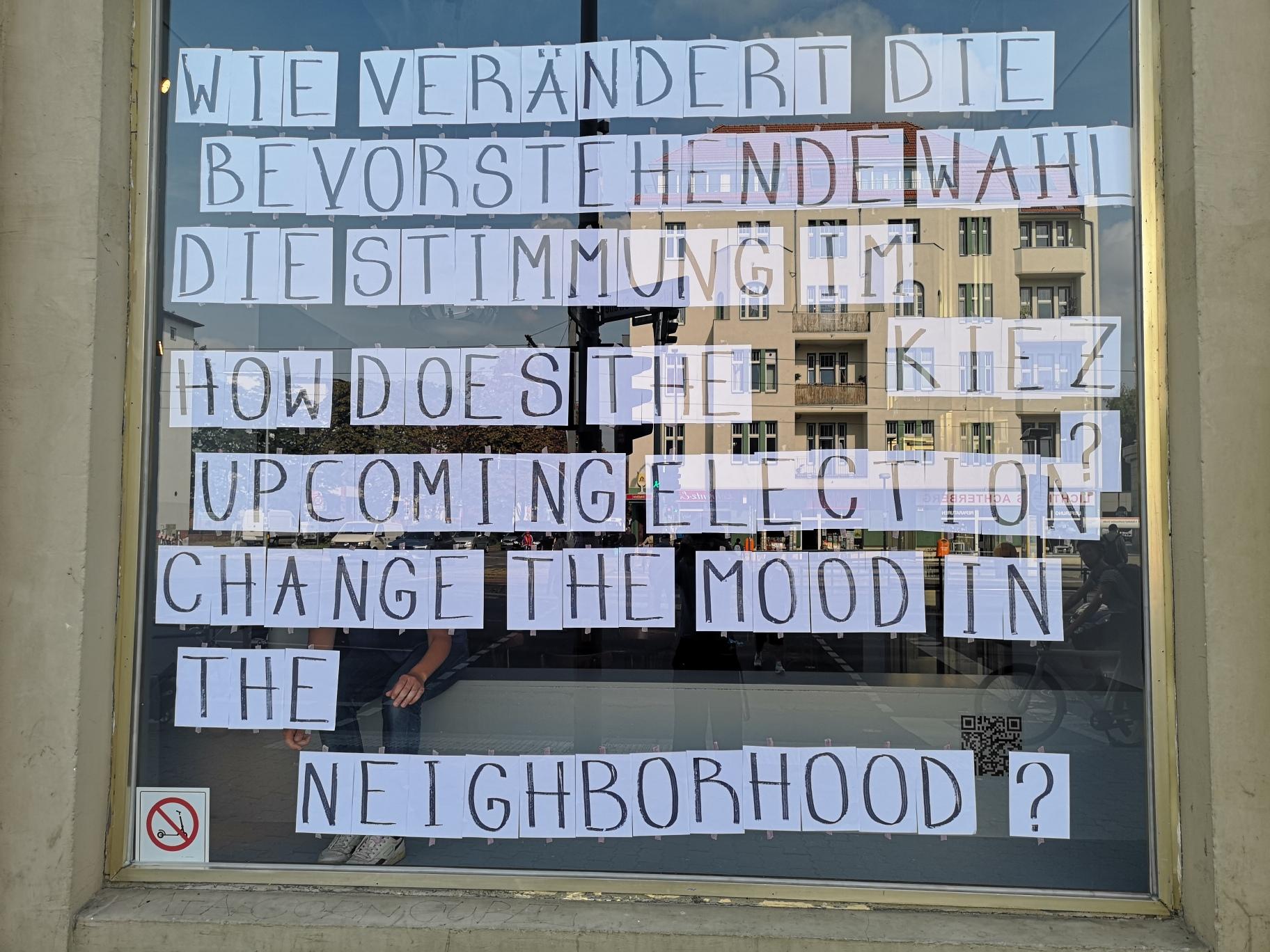 Schaufenster der Schaubude, auf dem auf einzelne Din-A4-Zetteln geschriebene Buchstaben zusammen die Frage ergeben: Wie verändert die bevorstehende Wahl die Stimmung im Kiez?