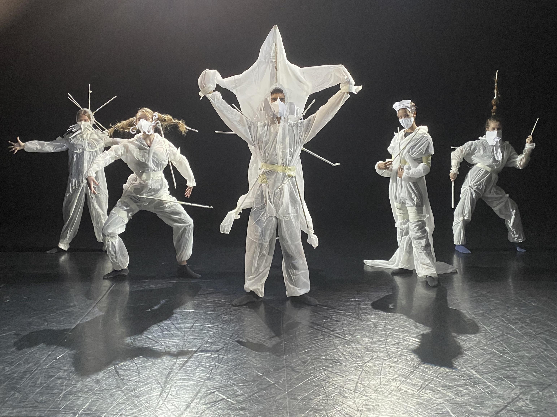 Fünf in weiße Schutzanzüge gekleidete Personen tragen futuristisch wirkende Masken aus Papier und Stäben