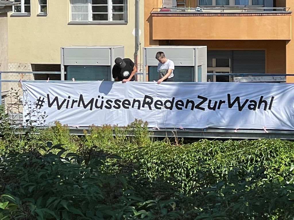 Two staff members of the Schaubude attaching a flag on the roof of the theatre that says #WirMüssenRedenZurWahl (We have to talk about the election)