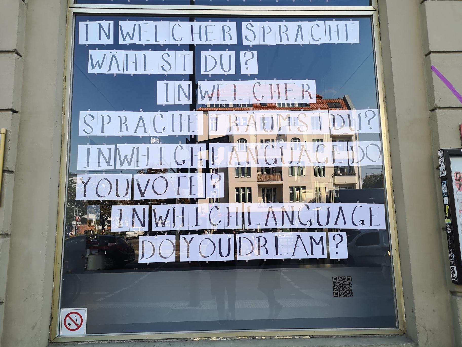 Schaufenster der Schaubude mit auf Din-A4-Zetteln geschriebenen Buchstaben, die zusammen die Fragen ergeben: In welcher Sprache wählst du? In welcher Sprache träumst du?
