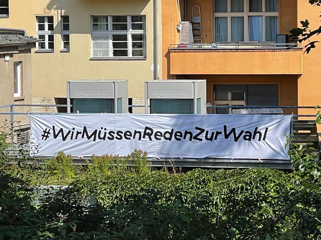 Banner auf dem Dach der Schaubude: #WirMüssenRedenZurWahl