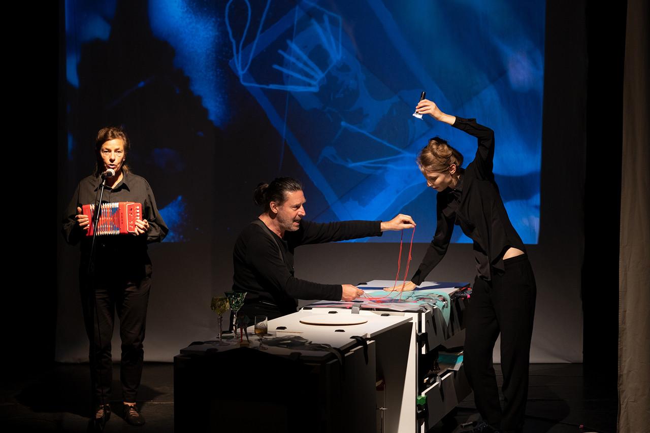 Zwei Spieler, ein Mann und eine Frau an einem Tisch mit Papiermaterialien. Hinter ihnen eine blaube Projektion an der Wand. Seitlich links steht eine weitere Peron mit einem Kinderakkordeon in der Hand.