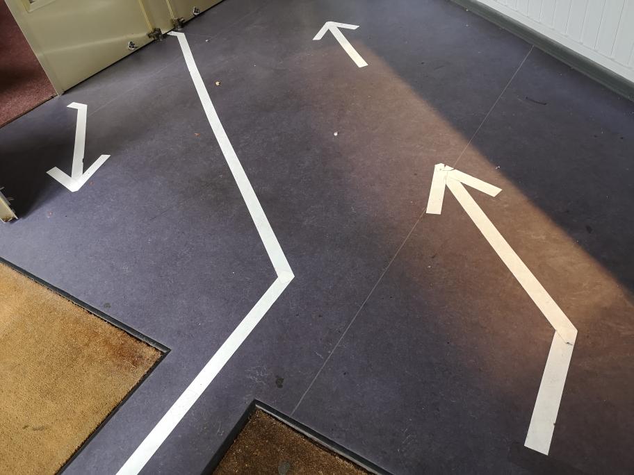Eingangsbereich der Schaubude mit auf dem Boden geklebten weißen Pfeilen.