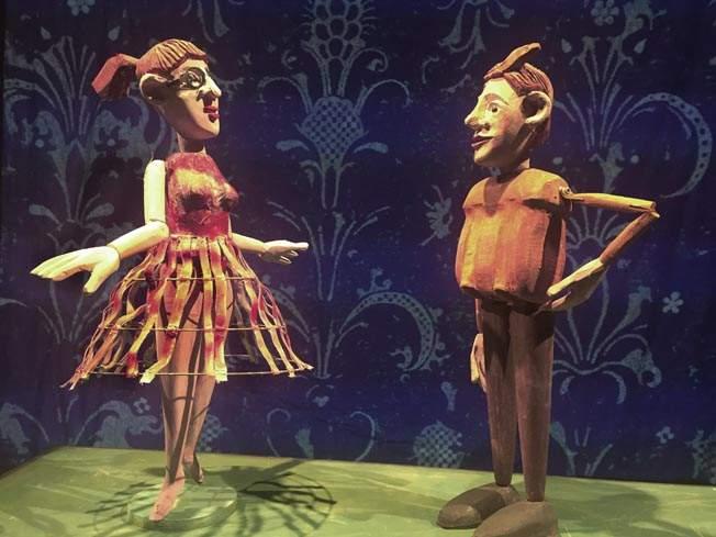 Zwei etwa 30 Zentimenter große Puppen aus Holz. Eine stellt ein Mädchen mit Bastrock dar, die andere einen Jungen mit roten Haaren. Sie scheinen im Gespräch miteinander zu sein.