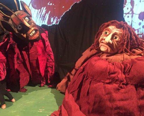 Links befindet sich eine Holzpuppe, die einen Teufel darstellt, rechts eine, die eine Hexe sein könnte. Beide haben einen grimmigen Gesichtsausdruck und rote Kleidung.