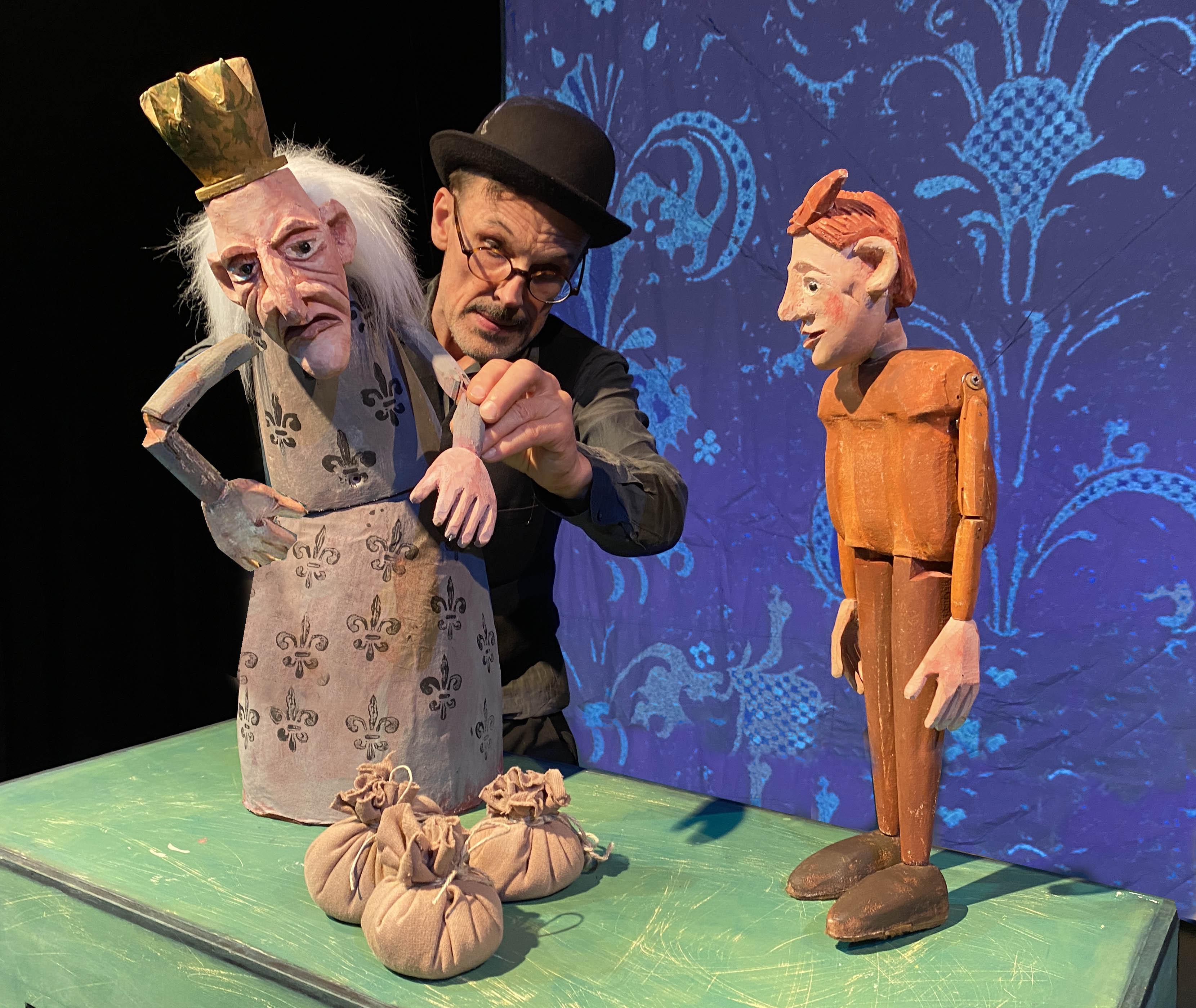 Ein Puppenspieler mit rundem Hut und Brille bewegt gerade den Arm einer Holzpuppe, die einen König darstellt. Daneben steht eine andere Holzpuppe mit roten Haaren. Im Hintergrund ist eine blau-gemusterte Leinwand.